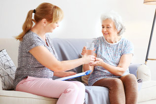 senior woman looking at her caregiver smiling