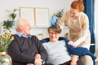 senior couple smiling at the caregiver