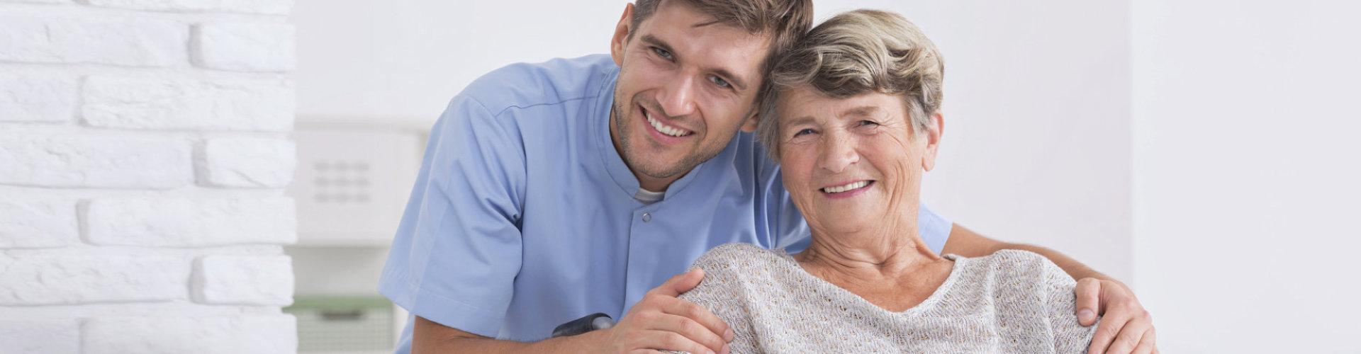 male caregiver hugging senior woman