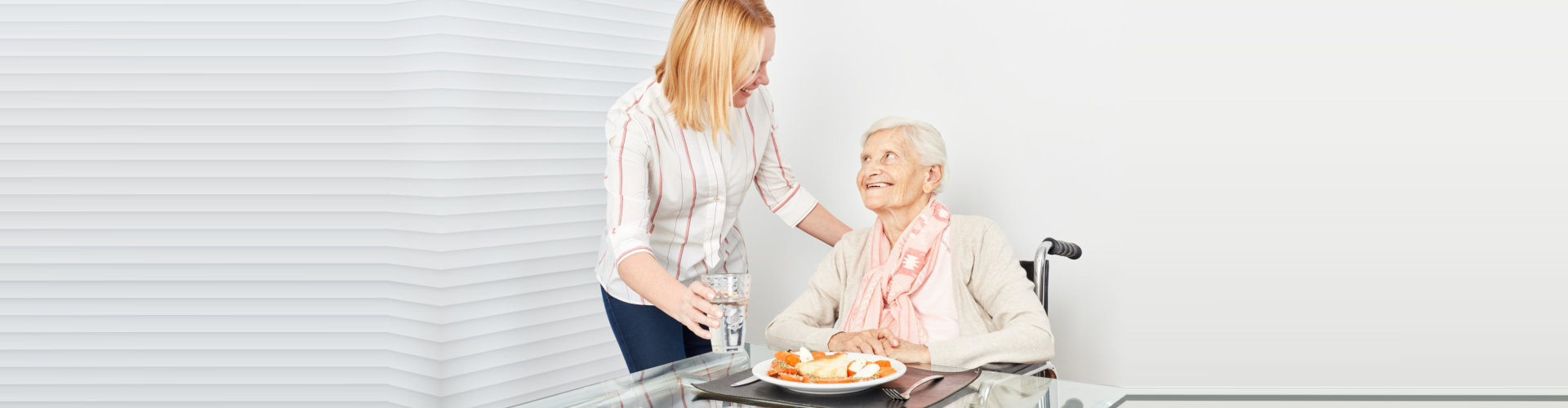 caregiver assisting senior woman in her meal